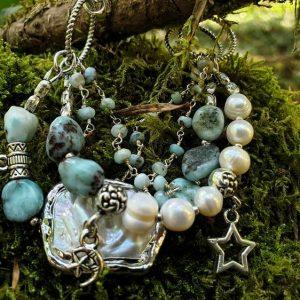 Bracelet en nacre, large perle biwa Keshi et larimar, les breloques sont des fées et des étoiles.