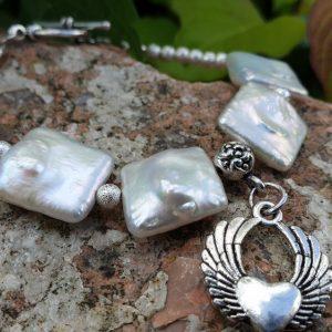 bracelet souple en perles biwa sur fil cablé, fermoir en T. Breloque charme coeur ailé.