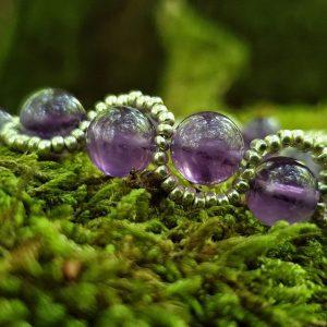 Bracelet en perles d'améthyste, il est tressé avec des perles de rocailles nacrées sur fil cablé.