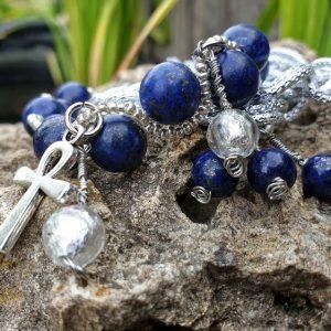 Bracelet lapis lazuli sur le thème Egypte, avec breloque Anubis et croix d'Ankh. Chaîne en double maillons argentés.