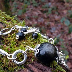 Bracelet avec une large perle en obsidienne dorée, pierre naturelle, montée sur une large chaîne en acier argenté.