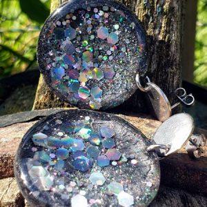 boucles d'oreilles en résine époxy, pigment noir métallique et paillettes holographiques dans l'esprit galaxie